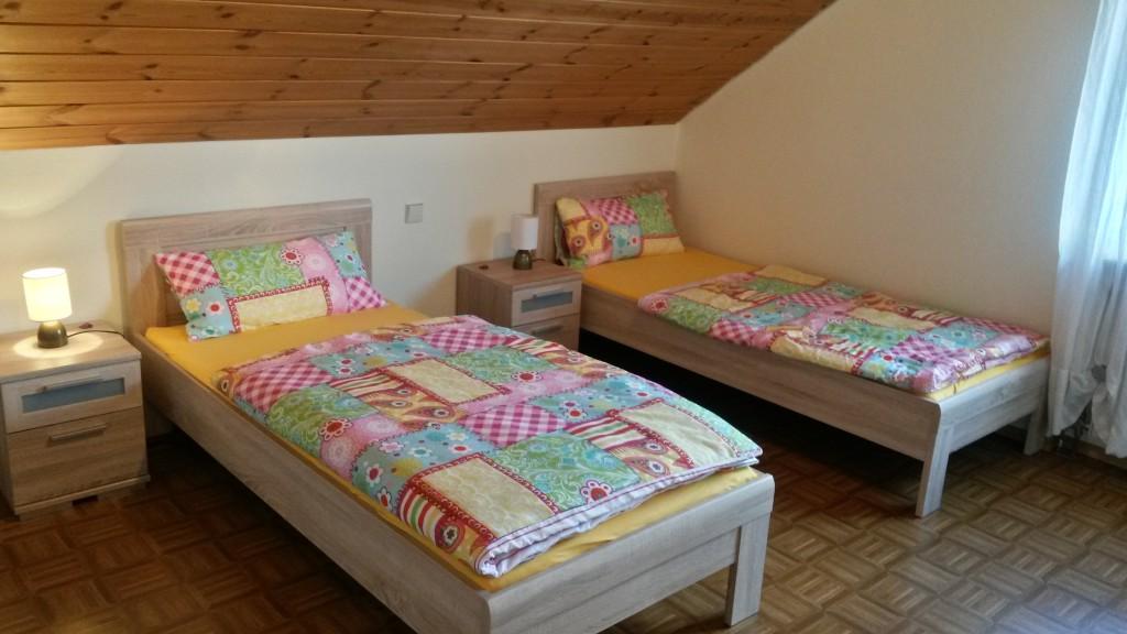 Schlafzimmer 1 - Zwei freistehende Betten, die auch zusammengestellt werden können, mit jeweils einem Nachttisch und einer Lampe