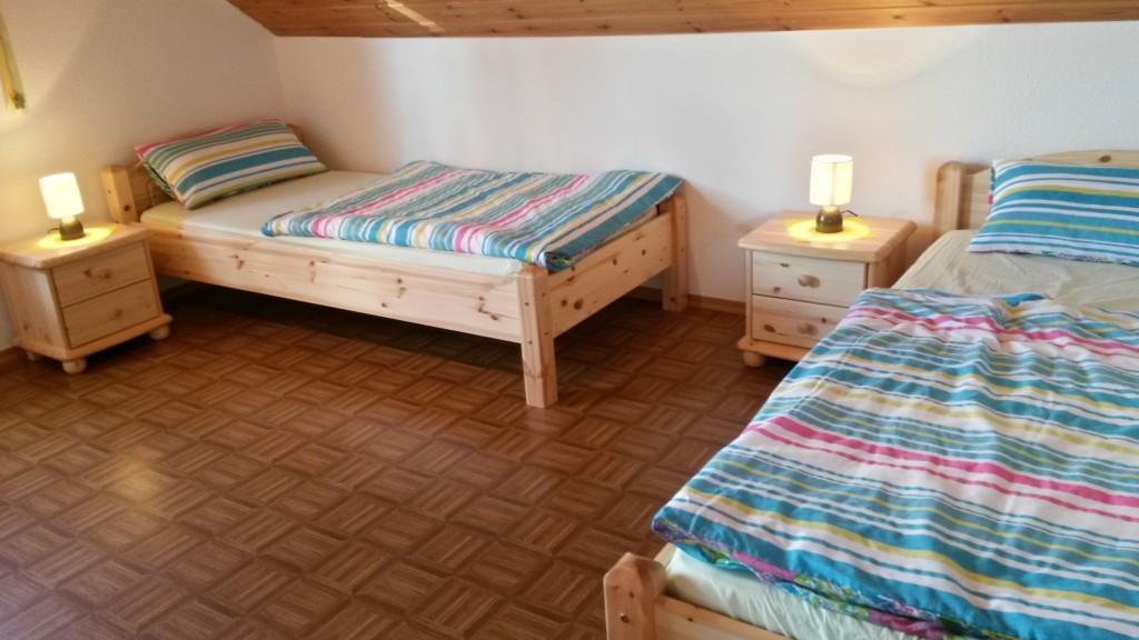 Zwei einzelstehende Betten, jeweils mit Nachtschränkchen und Lampe